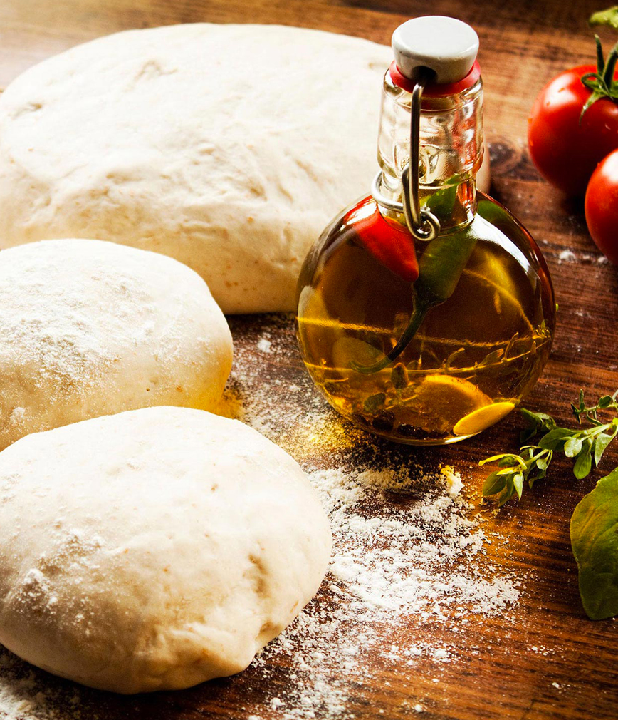 Pizza dough laid out on wooden table